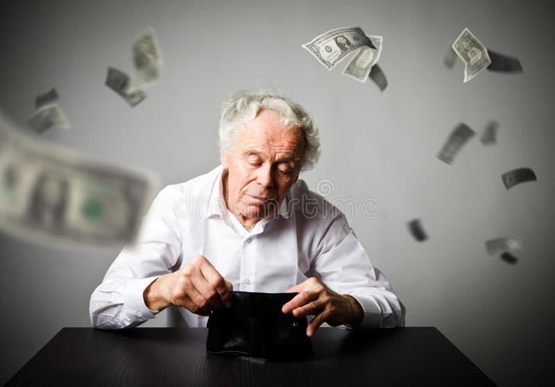 Old man in white and empty wallet. Accounting and taxes. Falling. Old man in white and empty wallet. Accounting and taxes concept. Falling dollars royalty free stock image