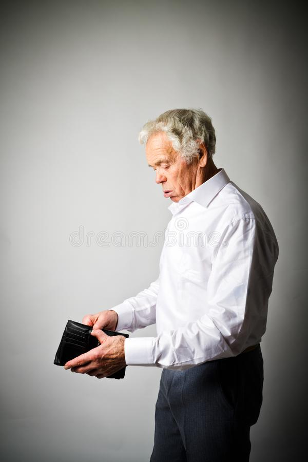Old man in white and empty wallet. Worried old man in white is looking at an empty wallet royalty free stock photography