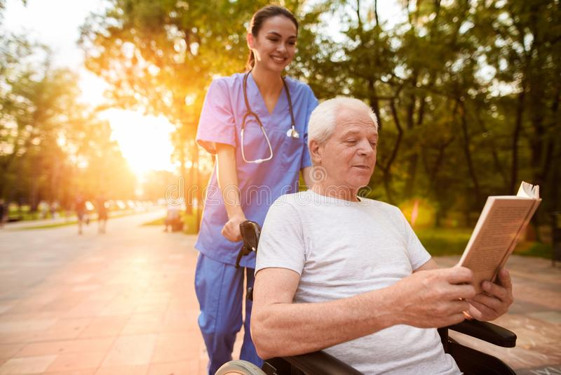 An old man who sits in a wheelchair and a nurse who is standing behind him reading a book in the park at sunset stock image