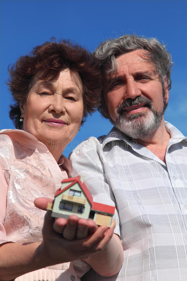 Old man and woman holding model of house. Old man and woman holding little model of house, blue sky stock image