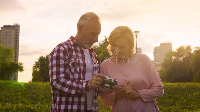 Old man and woman viewing photos on modern camera in park at sunset, photoshoot stock image