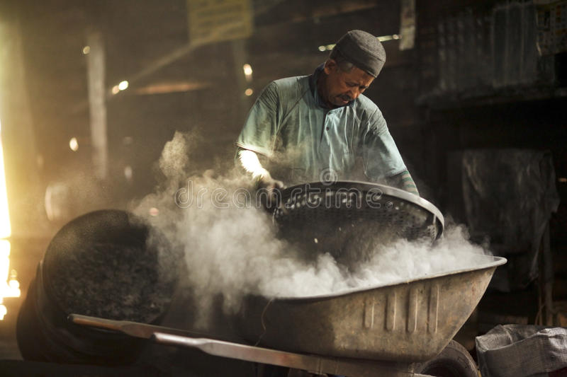 Old man working in dusty at charcoal factory royalty free stock images
