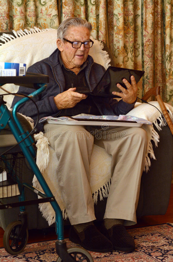 Old man working with laptop computer at home stock images