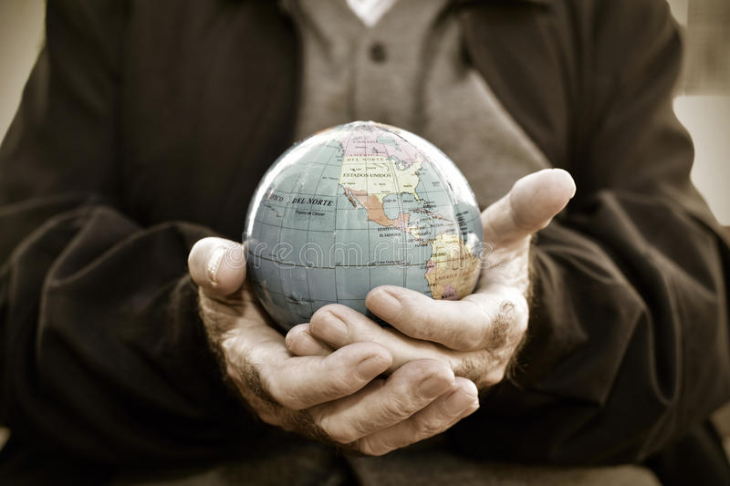 Old man with a world globe in his hands royalty free stock image