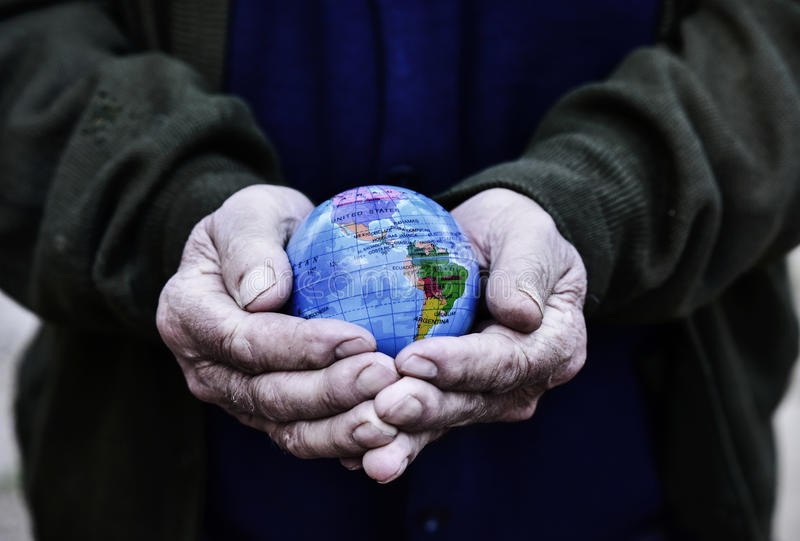 Old man with a world globe in his hands royalty free stock photography