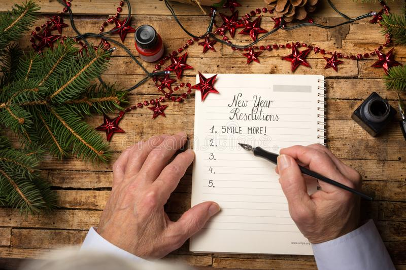 Old man writing new year resolutions. Old man making a list of new year resolutions on a decorated table royalty free stock photography