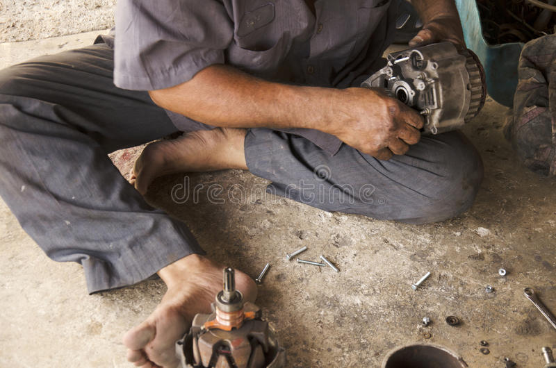 Old man 60 year thai people professional automotive motor mechanic repair and inspecting the alternator in car. At local shop on May 19, 2016 in Samut Sakhon stock photo