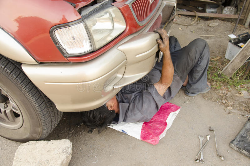 Old man 60 year old thai people professional automotive motor mechanic repair and inspecting the alternator in car. Old man 60 year thai people professional royalty free stock images
