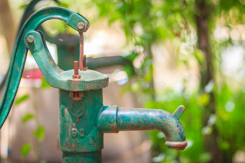 Old manual water pump (Lever pump). Vintage cast iron water pump stock image