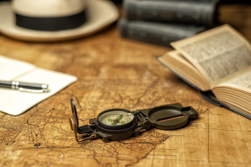 Old map with compass. Old expedition map with compass notebook, books and panama hat stock photo