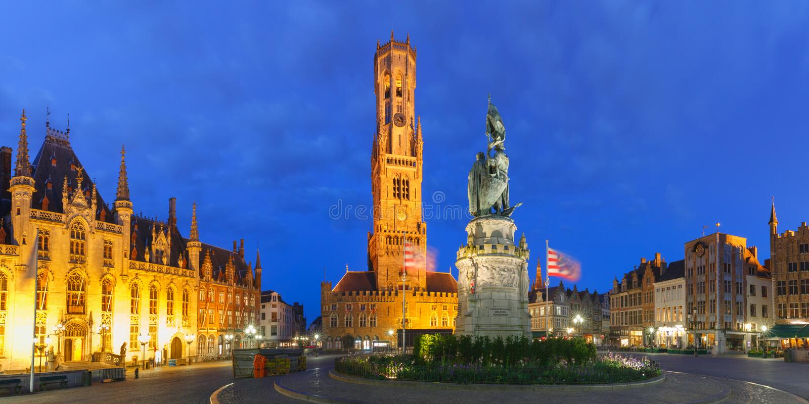 Old Market square in Bruges, Belgium. Panoramic view of Tower Belfort and statue of Jan Breydel and Pieter de Coninck on the Grote Markt or Market Square during stock images