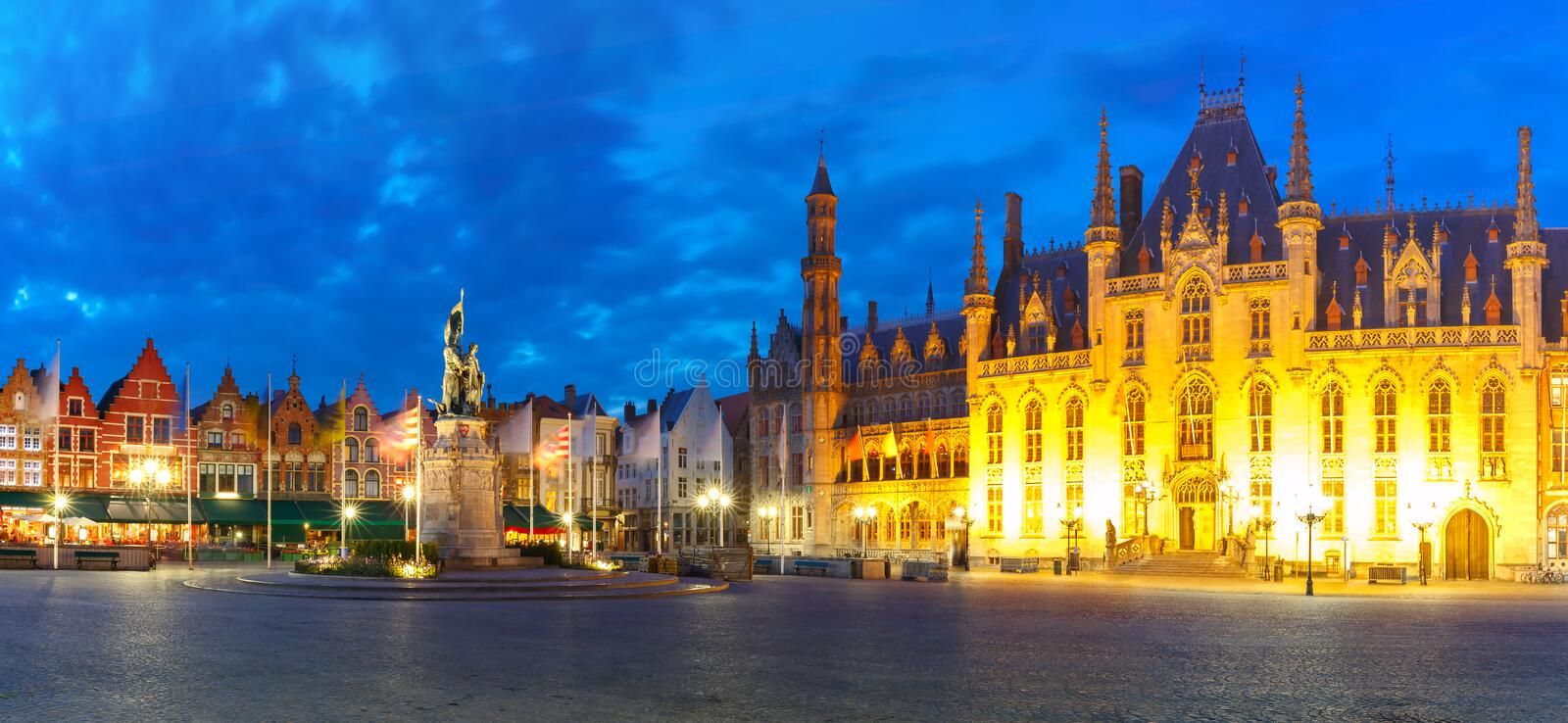 Old Market square in Bruges, Belgium. Panoramic view of typical Flemish colored houses and statue of Jan Breydel and Pieter de Coninck on the Grote Markt or stock photos