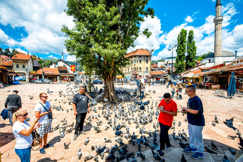 Old market square in Sarajevo. SARAJEVO, BOSNIA - HERZOGOVINA - CIRCA JUNE 2015: Crowded old market squire with pigeons on the north bank of the river Miljacka royalty free stock photos