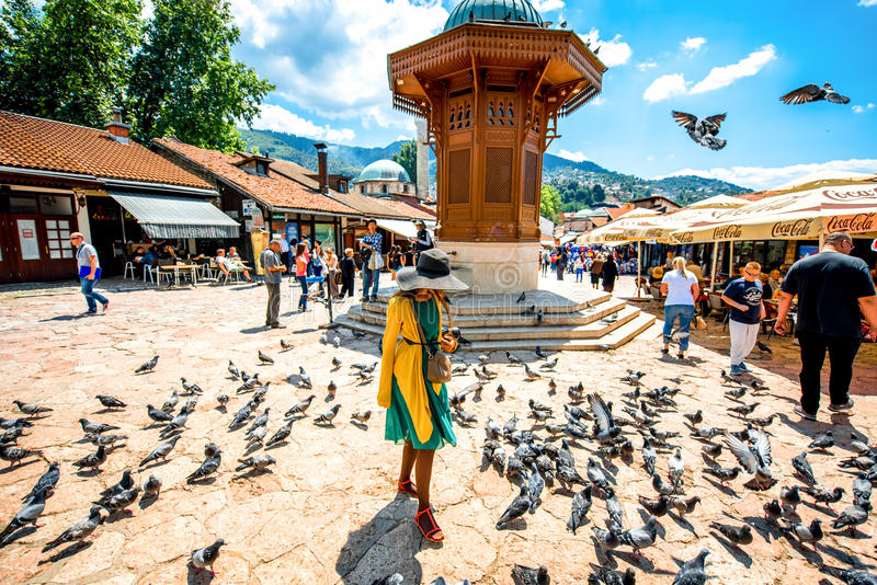 Old market square in Sarajevo. SARAJEVO, BOSNIA - HERZOGOVINA - CIRCA JUNE 2015: Crowded old market squire with pigeons and Sebilj fontain on the north bank of royalty free stock photography