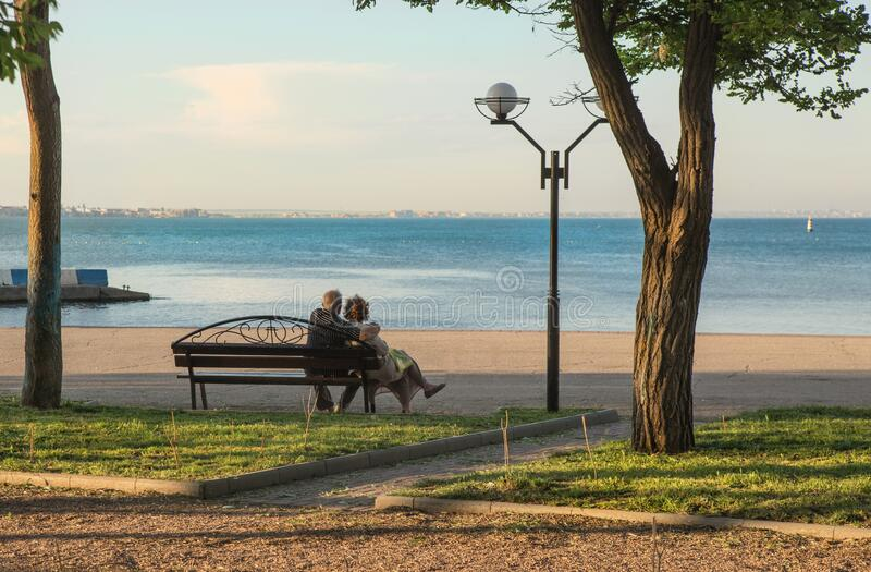Old married couple sit embracing on a bench on the embankment. By the sea stock photo