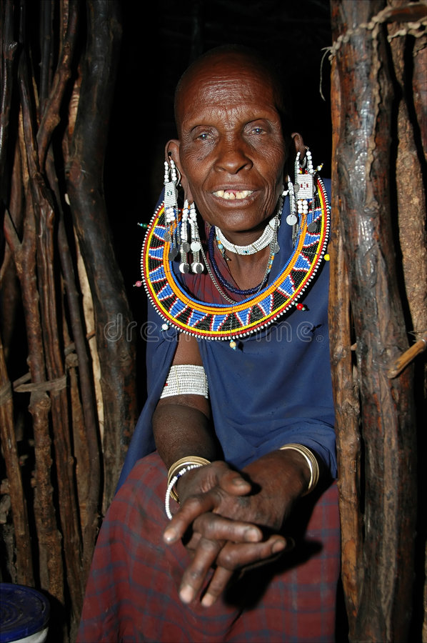 Old Masai in his wooden house - portrait stock photography