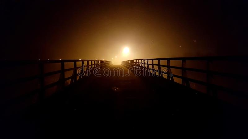 Wooden bridge at night surrounded with fog and city lights in background. Old massive wooden bridge with wooden handrails at night surrounded with thick fog and stock photos