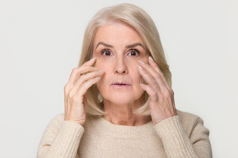 Old mature woman looking at camera worried about face wrinkles royalty free stock images