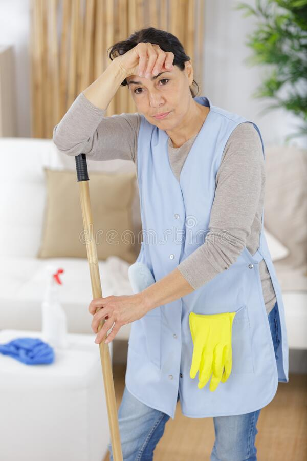 Old mature woman tired after house chores royalty free stock image