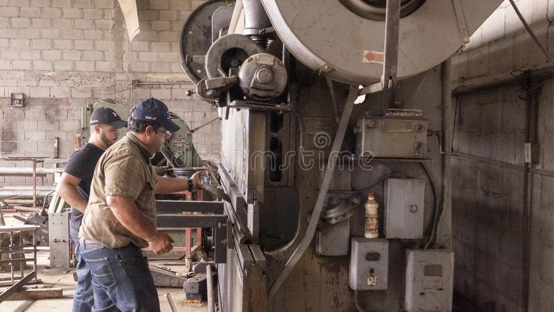 Old mechanical press brake industrial equipment maneuver by workers, La Paz, Mexico - December, 15th ,2017 stock image