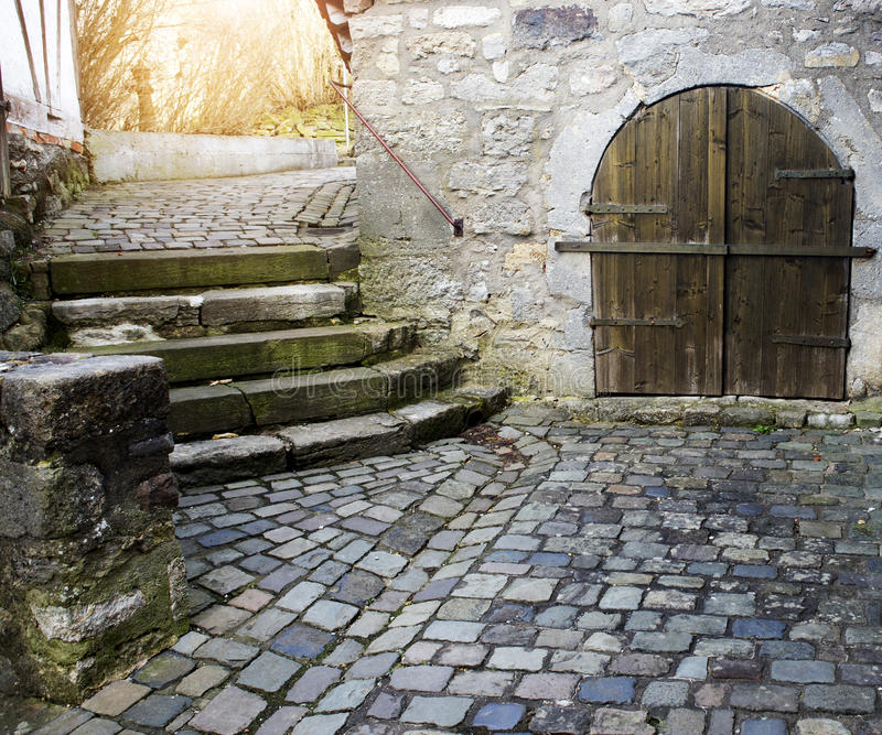 Old medieval cobblestone road and stone building royalty free stock images