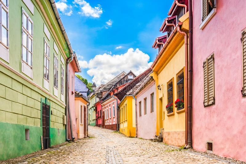 Old medieval cobblestone stree with colorful houses in Sighisoara, Transylvania, Romania royalty free stock images