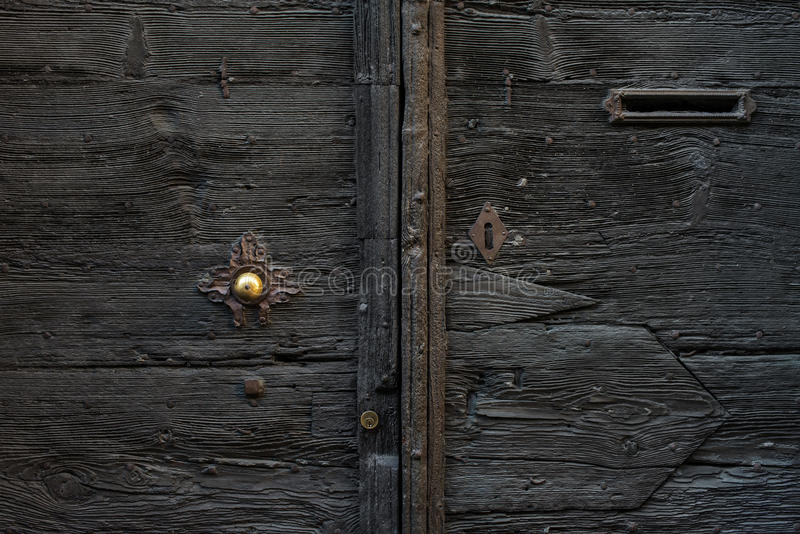 Old medieval italian wooden door with metal handle and a mail slot. royalty free stock images