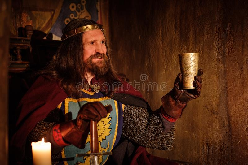 Old medieval king with goblet of wine on the throne in ancient castle interior. royalty free stock image