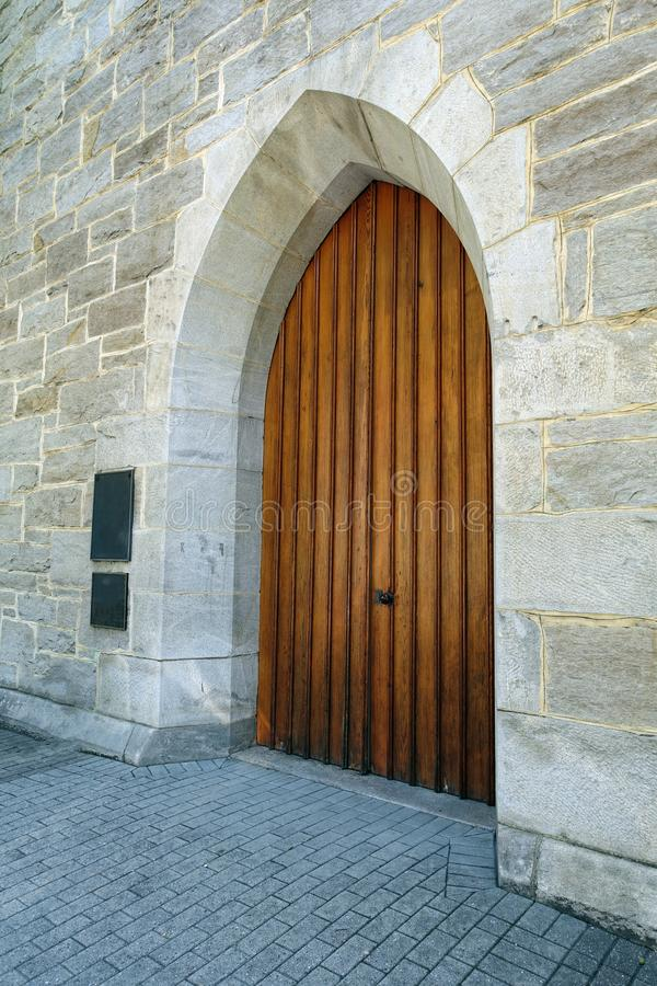 Old Medieval Wooden Door Surrounded by Stone Walls. Old Medieval Wooden Door on the Side of a Stone Building stock images