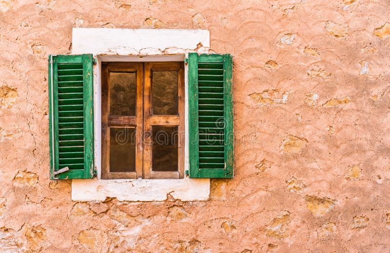 Wood window with open green shutters and rustic wall. Old mediterranean rustic house with open wooden window shutters and wall background with copy space royalty free stock images