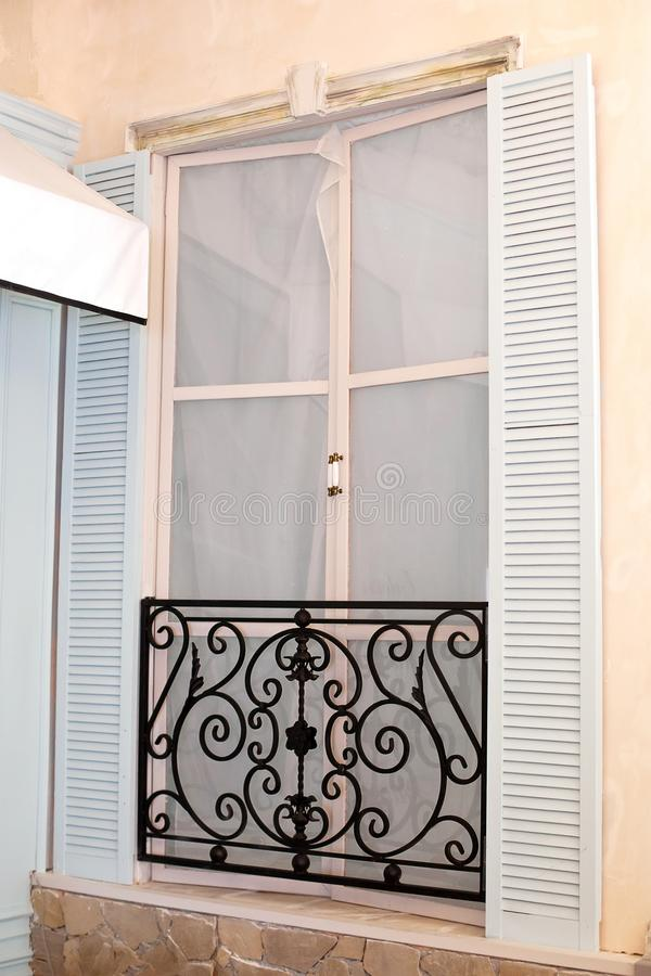 Old mediterranean window. French doors with wrought-iron balconies. A tiny balcony with wrought iron railings against a cream ston. E building with open shutters stock photo