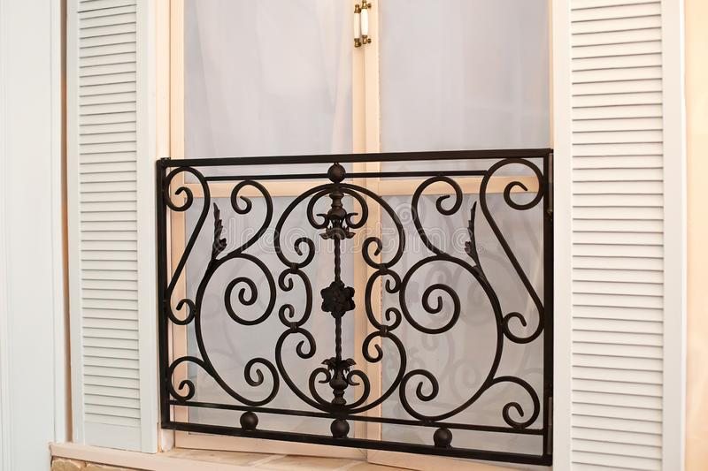 Old mediterranean window. French doors with wrought-iron balconies. A tiny balcony with wrought iron railings against a cream ston. E building with open shutters stock photos