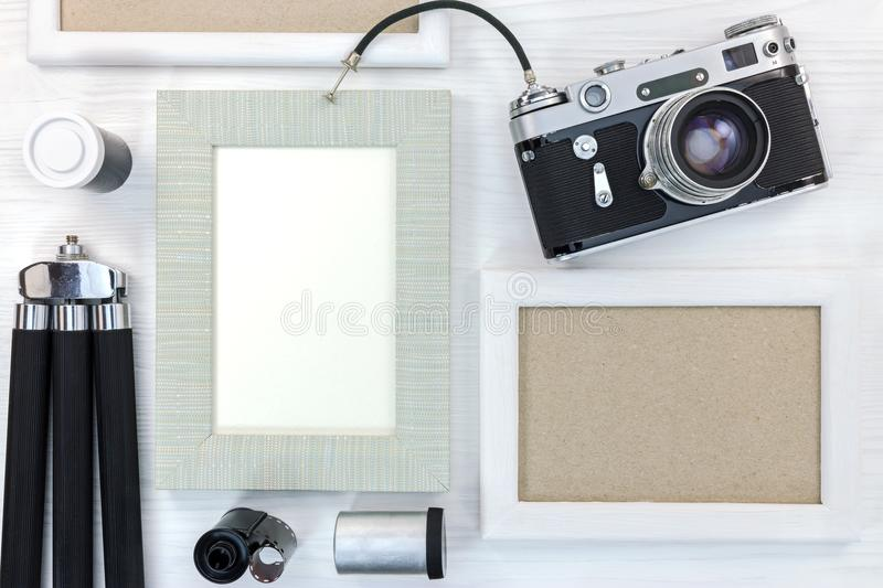 old memories concept - retro camera and empty photo frames on white wooden desk royalty free stock images
