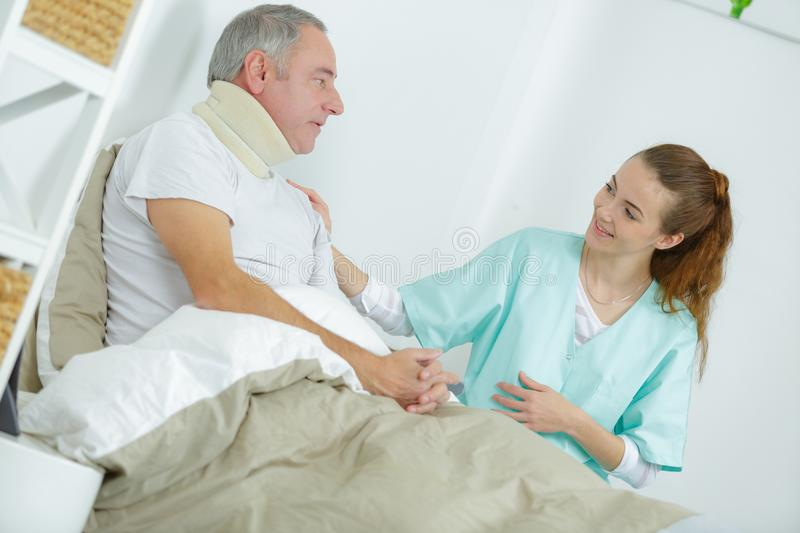 Old man in bed with nurse touching arm. Old men in bed with nurse touching his arm stock photos