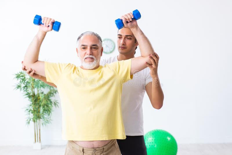 Old man doing exercises indoors. The old men doing exercises indoors stock photography