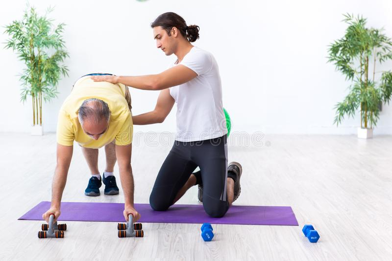 Old man doing exercises indoors. The old men doing exercises indoors stock photos