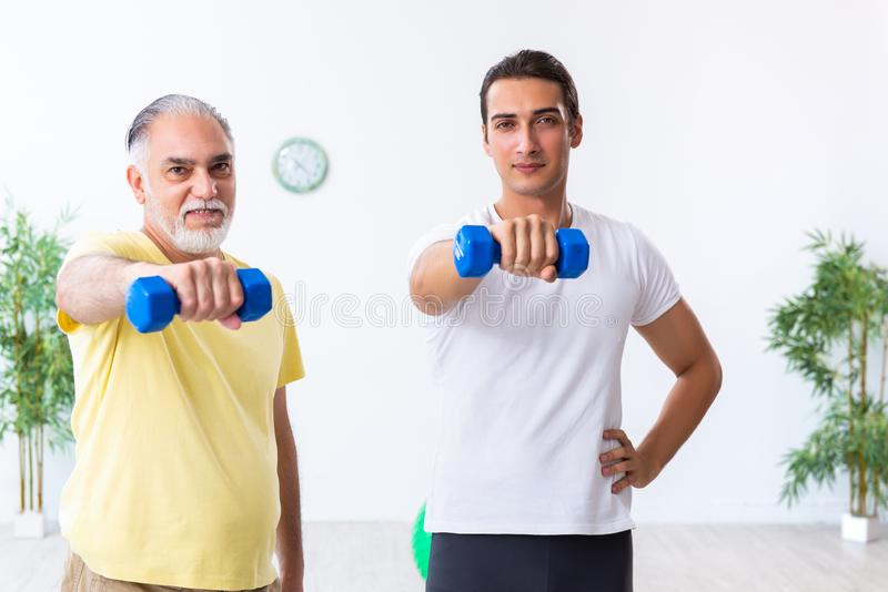 Old man doing exercises indoors. The old men doing exercises indoors royalty free stock photography