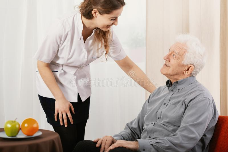 Old man in nursing home with helpful carer royalty free stock photography