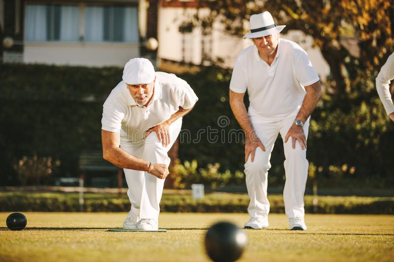 Old men playing a game of boules royalty free stock photography