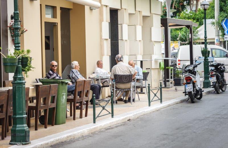 Old men sit in street cafe in Sitia town on Crete island, Greece. SITIA, CRETE, GREECE - JUNE 2016: Old men sit in street cafe in Sitia town on Crete island stock image