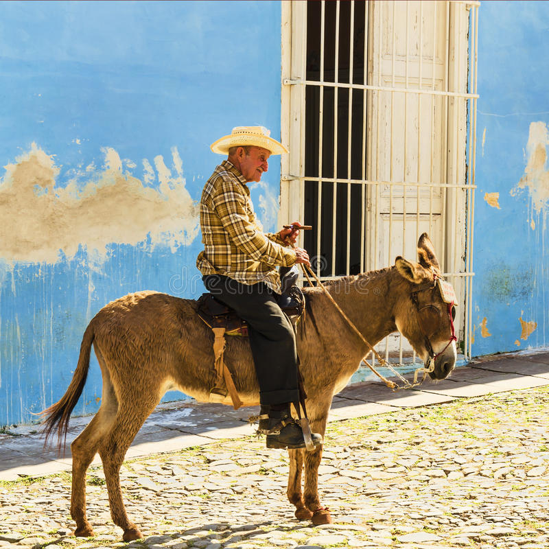 Old men sits on a donkey on the cobblestone street of Trinidad in Cuba stock photo