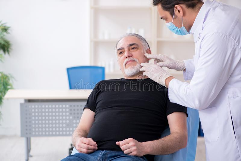 Old man visiting young doctor for plastic surgery. The old men visiting young doctor for plastic surgery stock photography