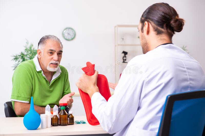 Old man visiting young male doctor gastroenterologist royalty free stock images