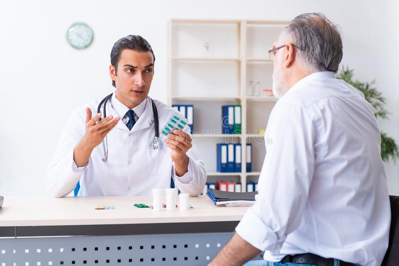 Old man visiting young male doctor. The old men visiting young male doctor stock photos