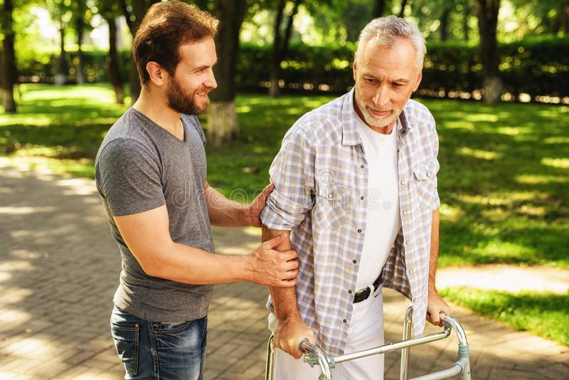 The old man walks through the park on walkers for adults. His son helps him stock photos