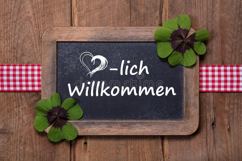 Old menu board with welcome message in german - clovers and ribbon on wooden background royalty free stock photos