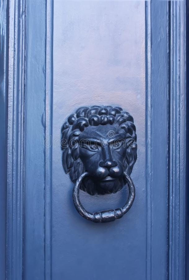 Old metal lion knocker on the door. Old metal antique door lion knocker on the home door royalty free stock photography