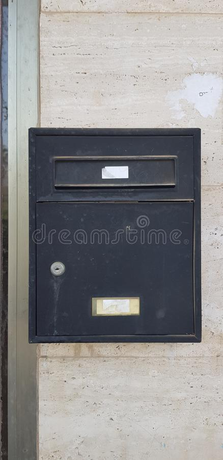Old metal black mail box closed with a key royalty free stock image