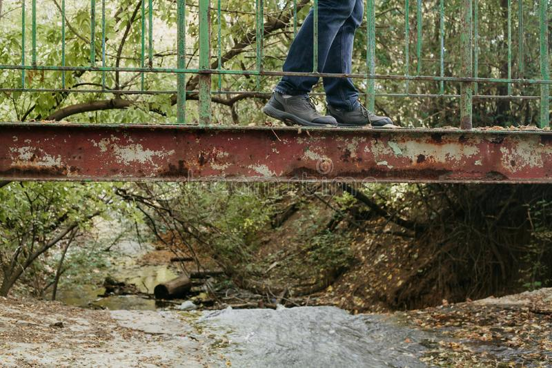 Legs of  man on old metal bridge. Side view. Old metal bridge over a small river against a background of green thickets. On the bridge are men`s legs in blue stock photo