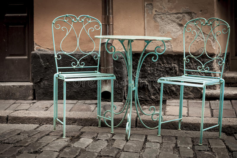 Old metal chairs. In the middle of a street stock photos